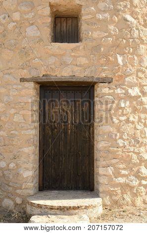 Wooden door on stone windmill in Belmonte a village of the province of Cuenca Castile-La Mancha Spain.