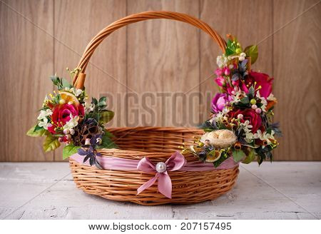 Designer basket is decorated with flowers. Wicker basket for celebrating Easter and other holidays. Decoration for home and interior