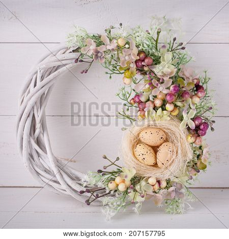 Decorative woven wreath is decorated with flowers and quail eggs. Wreath for pecker's Easter holidays