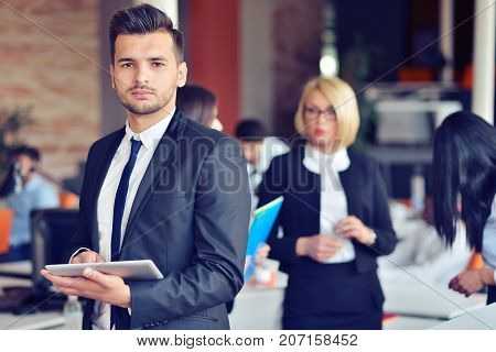 Midsection of businessman using digital tablet in office.