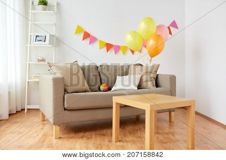 celebration and interior concept - sofa with cushions and table at cozy home room decorated for birthday party