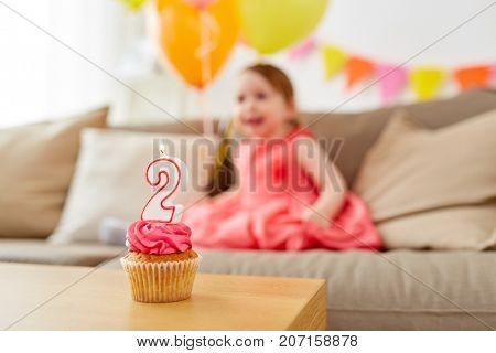 childhood and celebration concept - birthday cupcake with candle for two year old baby girl at home party