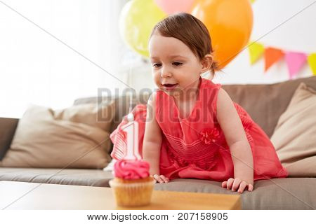 childhood, holidays and people concept - happy baby girl with cupcake on birthday party at home