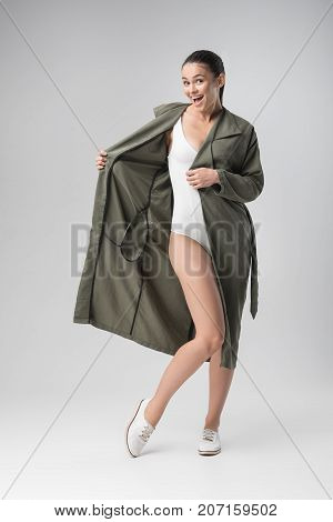 I am proud of my figure. Full length portrait of sexy young slim girl is posing with coat while showing her underwear. She is looking at camera and laughing. Isolated