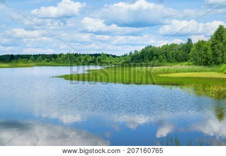 Bright summer landscape. Beautiful lake with forest and cloudy sky