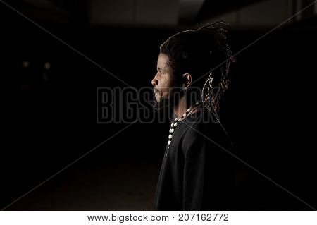 Profile portrait of a dark skinned man dressed in black clothes on the dark background