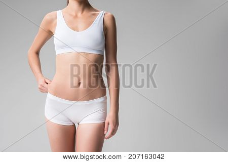I do not like my waist. Close up of slim body of young woman touching her waist with dissatisfaction. Perfection concept. Isolated and copy space