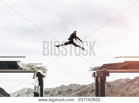 Business woman jumping over huge gap in concrete bridge as symbol of overcoming challenges. Skyscape and nature view on background.