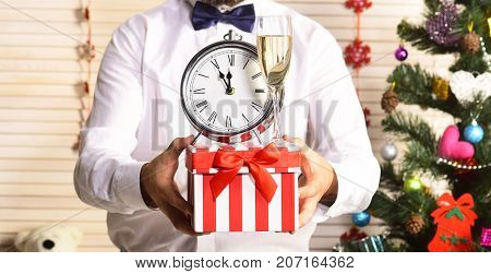 Man Holds Clock Showing Almost Midnight. New Years Eve Attributes