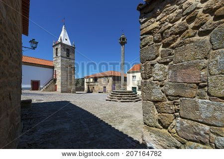 View of the central square of the historic village of Castelo Mendo in Portugal with a church and pillory; Concept for travel in Portugal