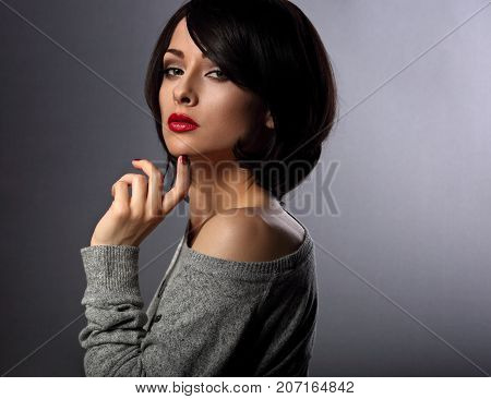 Sexy Beautiful Makeup Woman With Short Hair Style, Red Lipstick Touching Her Hair On Dark Shadow Bac