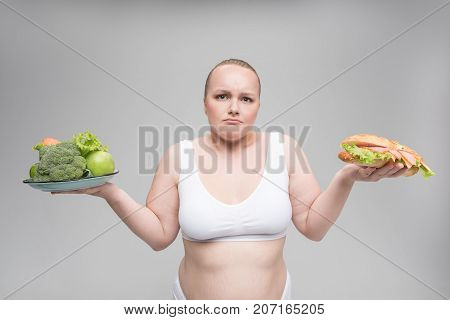 What to choose. Portrait of puzzled thick girl holding healthy and unhealthy food. She is wearing white underclothing. Isolated