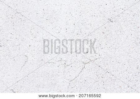 Smooth white concrete wall with thin fissures in different directions