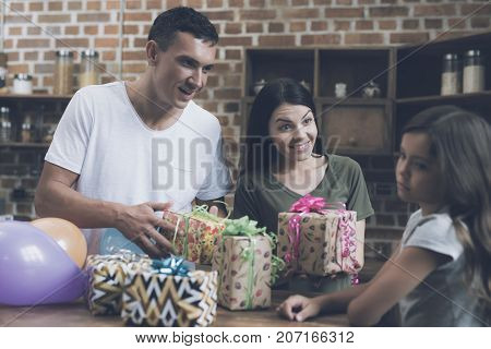 A Man And A Woman Give Gifts To A Sad Girl Who Turns Away From Them