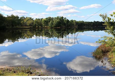 Beautiful sky, clouds, and trees reflected in the rippling water.
