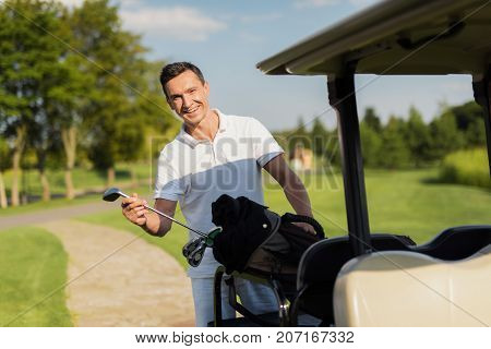 A Smiling Man Pulls Out Of A Bag With Sticks, A Golf Club. Bag Lies On The Luggage Compartment Of Th