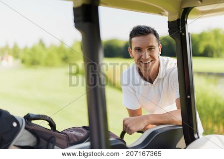 Part Of The Golf Cart In The Foreground. A Man Stands Behind Him And Smiles