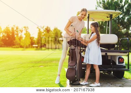 A Girl And A Woman Get The Golf Clubs Out Of The Bag