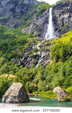 Giant Rjoandefossen waterfall by the Flam to Myrdal Railway Line Norway in sanny summer day.