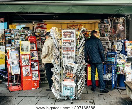 PARIS FRANCE - OCT 3 2017: People Seniors buying international newspapers at kisok with socking title photos at about the 2017 Las Vegas Strip shooting in United States with about 60 fatalities and 527 injuries