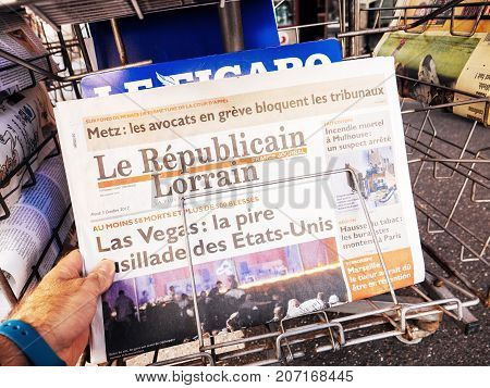 PARIS FRANCE - OCT 3 2017: Man buying Le republicai Lorrain newspaper with socking title and photo at press kiosk about the 2017 Las Vegas Strip shooting in United States with about 60 fatalities and 527 injuries