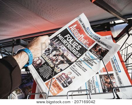 PARIS FRANCE - OCT 3 2017: Man buying Aujord'hui French newspaper with socking title and photo at press kiosk about the 2017 Las Vegas Strip shooting in United States with about 60 fatalities and 527 injuries