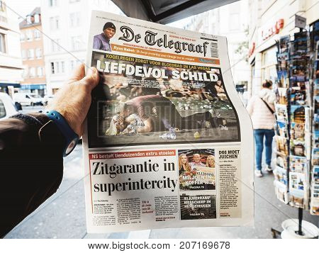 PARIS FRANCE - OCT 3 2017: Man buying De Telegraaf newspaper with socking title and photo at press kiosk about the 2017 Las Vegas Strip shooting in United States with about 60 fatalities and 527 injuries