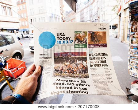 PARIS FRANCE - OCT 3 2017: Man buying USA Today newspaper with socking title and photo at press kiosk about the 2017 Las Vegas Strip shooting in United States with about 60 fatalities and 527 injuries