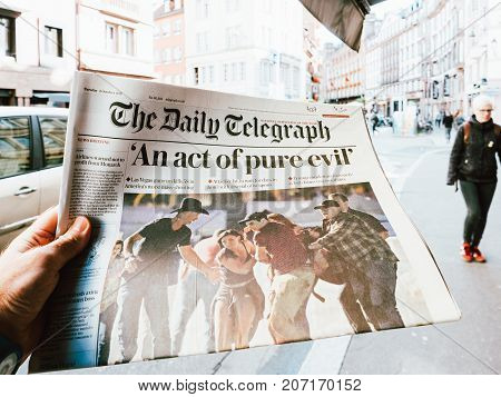 PARIS FRANCE - OCT 3 2017: Man buying The Daily Telegraph newspaper with socking title Pure Evil and photo at press kiosk about the 2017 Las Vegas Strip shooting in United States with about 60 fatalities and 527 injuries