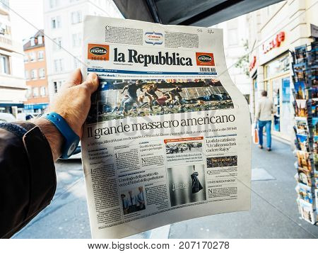 PARIS FRANCE - OCT 3 2017: Man buying La Republica Italian press newspaper with socking title and photo at press kiosk about the 2017 Las Vegas Strip shooting in United States with about 60 fatalities and 527 injuries