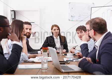 Manager with employees meeting, successful team with female boss. Multiethnic. Office discussion, communication with partners at the desk, planning development strategy. Crop