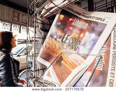 PARIS FRANCE - OCT 3 2017: Man buying Liberation French newspaper with socking title and photo at press kiosk about the 2017 Las Vegas Strip shooting in United States with about 60 fatalities and 527 injuries