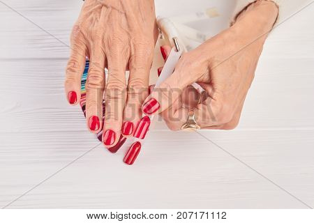 Red nail sample in female hand. Old woman hand with red manicure holding red nail sample. Well-groomed femal hands in beauty salon.