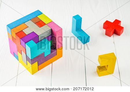 Concept of decision making process. Concept of creative logical thinking. Different geometric shapes wooden blocks on white wooden background. Geometric shapes in different colors.