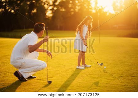 The Girl Is Preparing To Make A Hit On The Ball, The Man Is Sitting Next To Him Squatting And Lookin