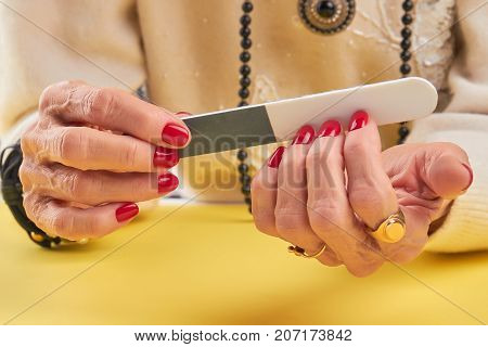 Woman filing manicured nails to herself. Old woman hands with red manicure filing nails with file on yellow background.