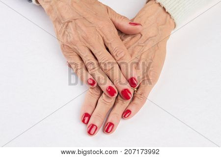 Female hands with red manicure. Senior woman hands with perfect red manicure isolated on white background. Nail and skin care.