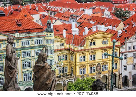 The facade of building in the classical style. Classic european architecture. Red tile roofs and christian statues