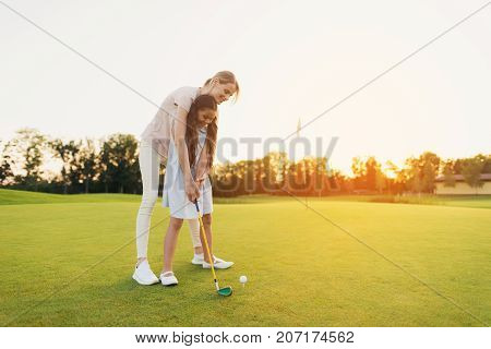A Woman Is Teaching A Girl To Play Golf. The Girl Is Preparing To Hit, The Woman Is Standing Behind