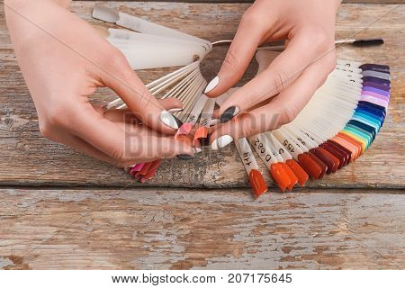 Woman hands holding summer nail samples. Young woman hands holding nails colors samples on vintage wooden background. Nail beauty salon.