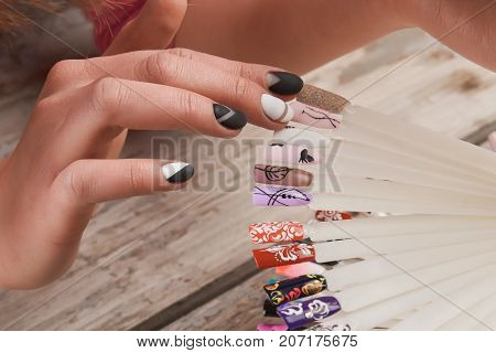 Woman choice of nail art design. Female hands selects color shellac nail polish close up. Nail beauty salon.