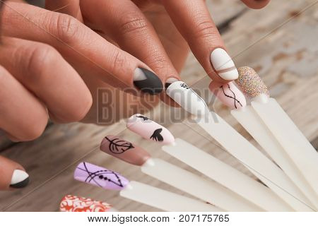Woman in nail salon choosing nail design. Close up of female hands selects nail color and design close up.
