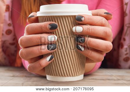 Manicured hands holding cardboard cup. Female hands with perfect manicure holding disposable cup of coffee. Time for beauty and relax.