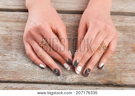 Young woman hands with stylish manicure. Female manicured hands with golden rings on old wooden background. Beauty salon and spa.