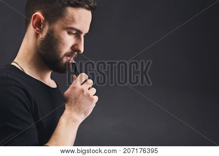 Man with vape at black studio background closeup. Young bearded guy smoking e-cigarette to quit tobacco. Nicotine free smoking and vapor concept, copy space, closeup
