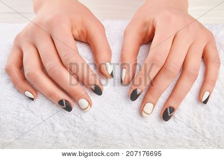 Manicured hands on white towel. Well-groomed female hands in spa salon close up. Hands and nail treatment. Stylish autumn manicure.