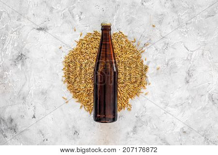 Grains of malting barley near beer bottle on grey background top view. poster