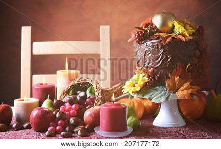 Beautiful Thanksgiving Fall table setting with Autumn theme chocolate cake cornucopia and candles.