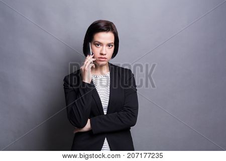 Thoughtful brunette woman in formalwear speaks on mobile phone, make call and conversation concept. Copy space