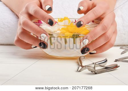 Female hands on manicure bath. Woman hands with stylish manicure on bowl with chrysanthemums, manicure tools.